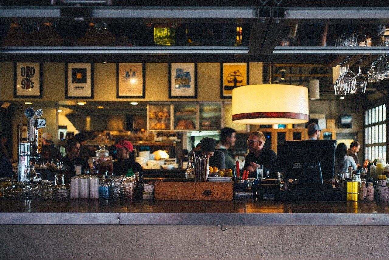 Ravintolan tiskin takaa kuvattu yleiskuva ravintolan sisätiloista. Tiskillä ravintolatarvikkeita, taustalla seinillä kehystettyjä taideteoksia.
