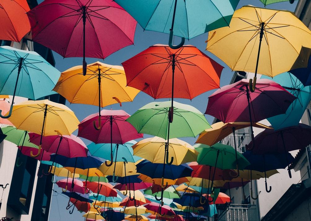 Värikkäitä sateenvarjoja roikkumassa naruista vasten taivasta, kuva taideinstallaatiosta.