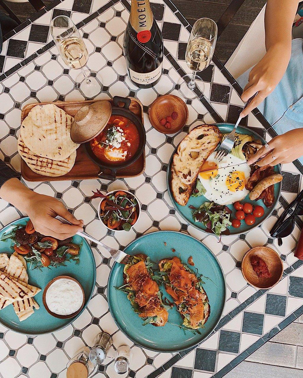 Kuvituskuva: jaettu lounaspöytä, jossa kaksi ihmistä syömässä
