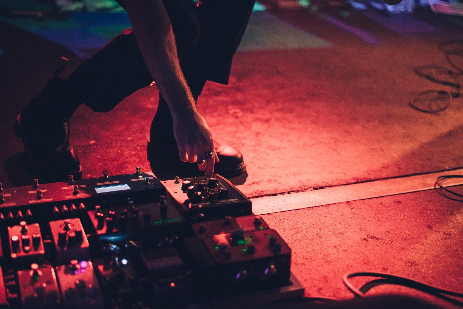 Kitaristi kumartuneena lavalla, käsi säätää maahan asetettuja efektipedaaleja.