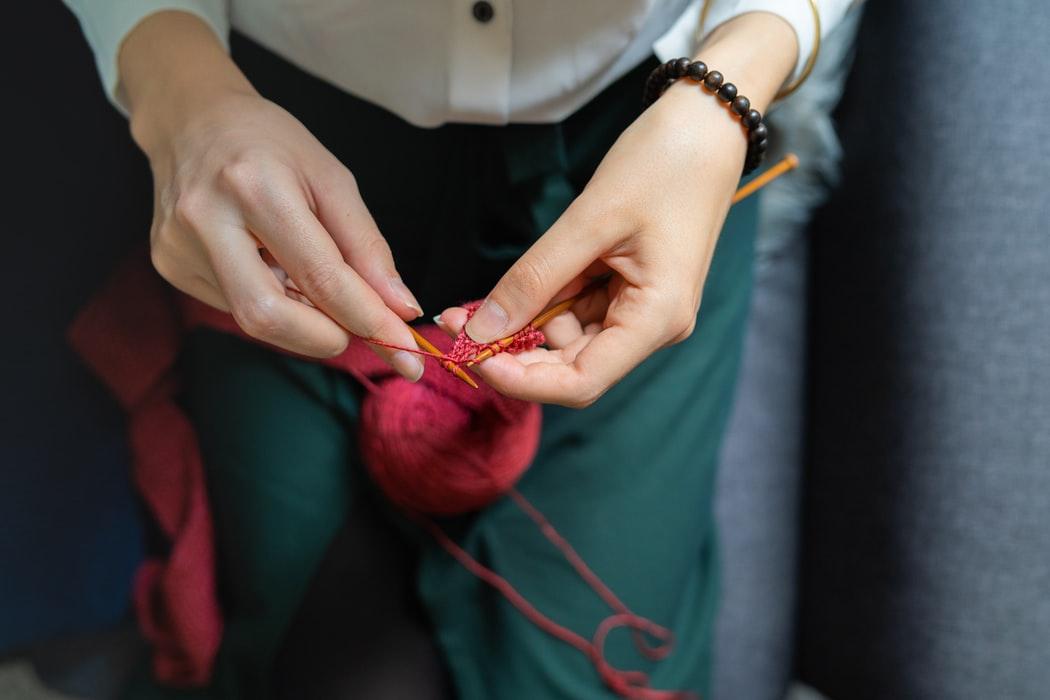 Henkilön kädet kutomassa vielä epäselvää esinettä punaisesta lankakerästä.